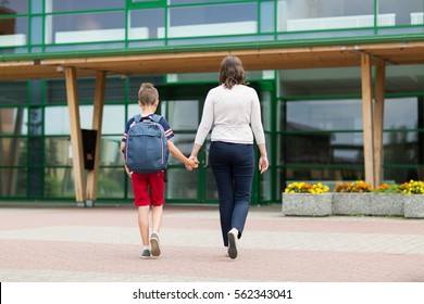 education, childhood, family and people concept - elementary student boy with mother going to school