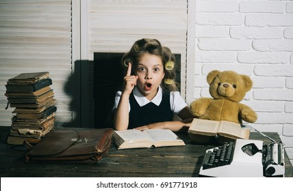 Education and childhood. Kid choose career of journalist or writer. Little baby secretary in cabinet or library. Small girl with curler in hair read book. Child with briefcase and typewriter on table.
