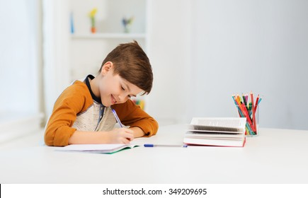 education, childhood, people, homework and school concept - smiling student boy with book writing to notebook at home