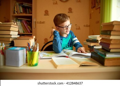 education, childhood, people, homework and school concept - bored student boy reading book or textbook at home