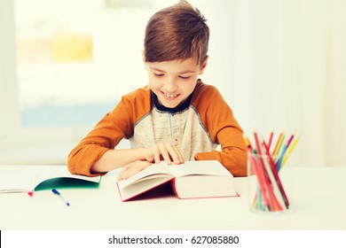 education, childhood, people, homework and school concept - happy student boy reading book or textbook at home