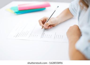education, children and school concept - little student girl taking test