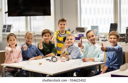 education, children, technology, science and people concept - group of happy kids building robots at robotics school lesson and showing thumbs up