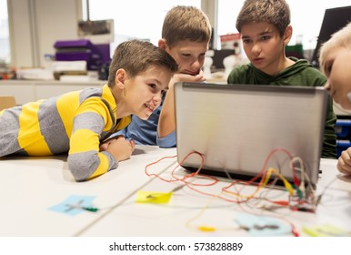 education, children, technology, science and people concept - group of happy kids with laptop computer playing with invention kit at robotics school lesson