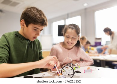 education, children, technology, science and people concept - happy kids building robots at robotics school lesson