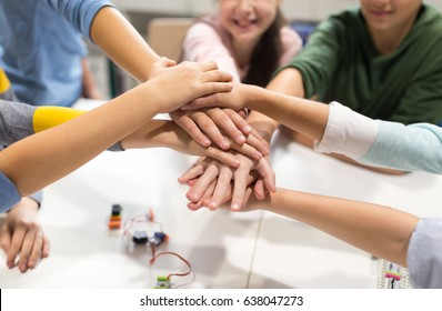 education, children, technology, science and people concept - group of happy kids building robots l at robotics lesson and holding hands together