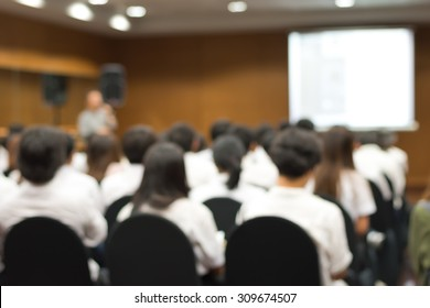 Education classroom blur background of university students sitting in a lecture hall or seminar room with teacher and white projector slide screen in front of class for back to school concept