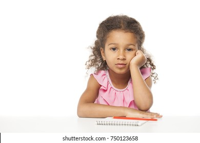 Education. Close up portrait of african little girl is sitting at the table with a notebook for drawing, isolated on white background