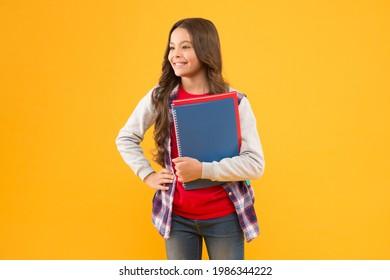 Bildung steht an erster Stelle. Glückliches Kind hält Studienbücher. Grundbildung. Zurück zur Schule.