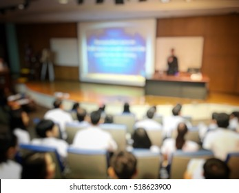 Education concept, Abstract blurred background image of students studying and discuss in large hall with screen and projector for showing information