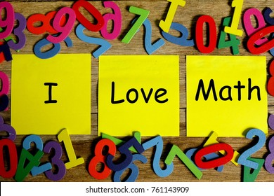 Education concept for blog title and header. Top view of yellow sticky notes written with I LOVE MATH on variety colors of wooden numbers background.