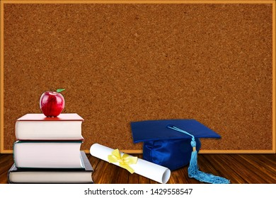 Education concept with blue graduation hat and diploma and stack of books with apple on cork board background. Copy space on corkboard.