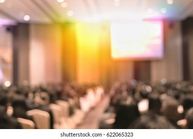 Education concept, blurred students studying in large hall with screen and projector for showing information