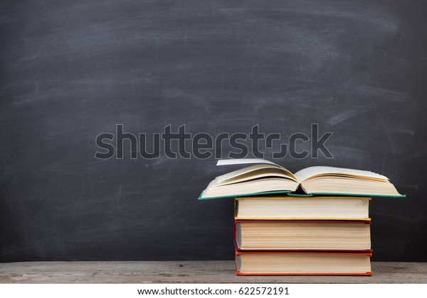 Education concept - books on the desk in the auditorium