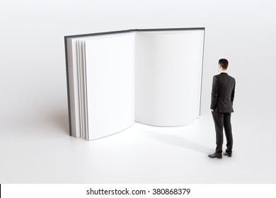 Education concept with businessman looking in blank white book pages, mock up