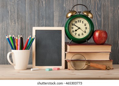 Education concept with chalkboard, books, alarm clock and supplies