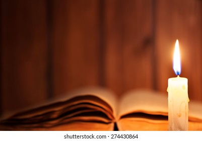 Education concept. Close-up view of old burning candle with shabby old book on wooden background. Focus on the candle