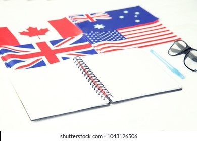 Education concept. English language learning. English speaking countries. Notebook, textbook, blue pen, glasses, four flags on a wooden table.