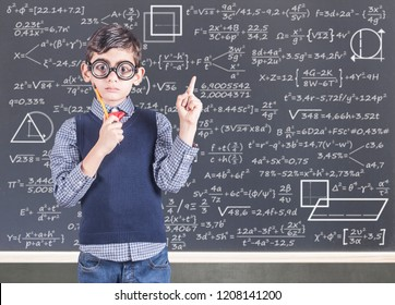 Education concept with funny geek school boy in front of a blackboard