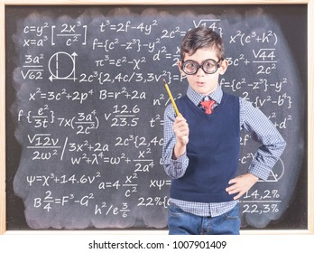 Education concept with funny smart school boy in front of a blackboard