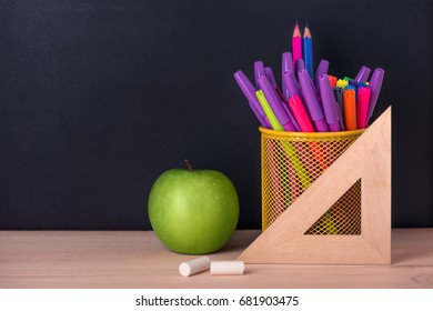 education concept with green apple, ruler or triangle, felt pens, chalks over black chalkboard background, close up