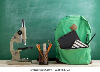 Education concept - green backpack, microscope, black notebooks and pencils on the background of the blackboard