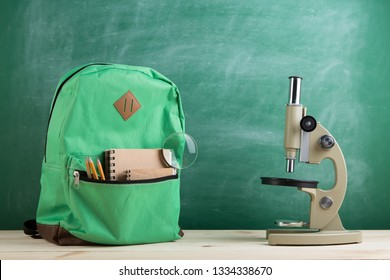 Education concept - green backpack, microscope, notebooks and pencils on the background of the blackboard