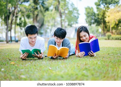 Education concept - Group of asian students intend to read books simultaneously on grass at the green garden during the summer.
