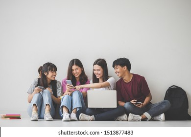 Education concept - Group of cheerful students sat on the floor with a laptop computer and smiled as the team happily looked at the camera. Teen classmates sit together on campus.