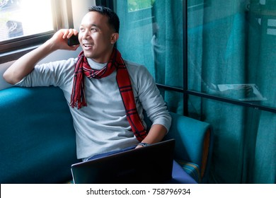 Education concept: A handsome man is overseas student. He sits on sofa and calling his family from foreign country. A charming man gets so happy when he talks to his family. It's the winter season.