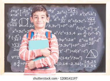 Education concept with happy school boy in front of a blackboard