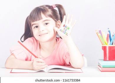 Education concept with happy school girl doing her homework having a hand drawn Back to school message