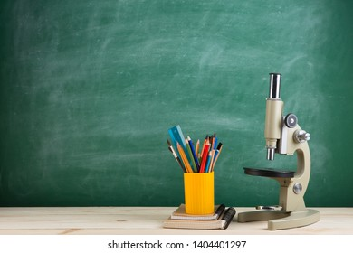 Education concept - microscope on the desk in the auditorium