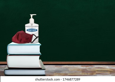 Education concept of New Normal in schools during Covid-19 pandemic with books, hand sanitizer and cloth face mask in classroom. Back to school items to stop coronavirus outbreak with copy space.