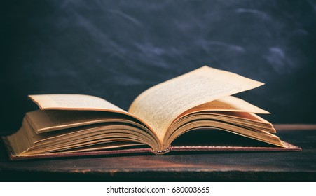 Education concept. Old book on blackboard background