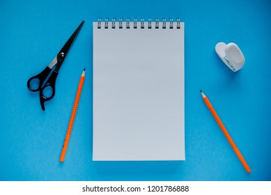 education concept orange pencils, sketchbook , scisots, puncher. Educational set on blue background.
