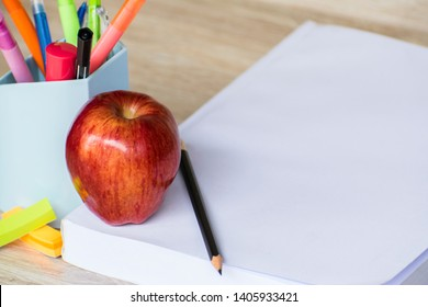 Education concept, Red aple write book colorful pens and global with wooden backgrounds.learning in twenty one century. Knowledge management. Innovation active for student.selective focus image.