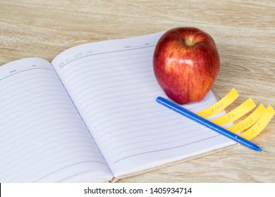 Education concept, Red aple write book colorful pens with wooden backgrounds.learning in twenty-One century. Knowledge management. Innovation active for student.selective focus image.
