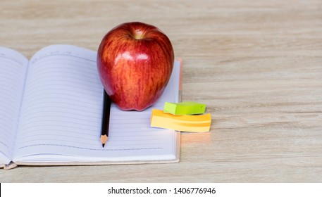 Education concept, Red aple write book colorful pens and global with wooden backgrounds.learning in twenty-One century. Knowledge management. Innovation active for student.selective focus image.