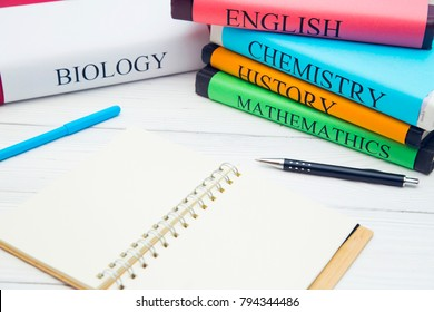 Education concept: school books on different subjects in bright covers and an opened notebook on a white wooden table, space for a text or product display
