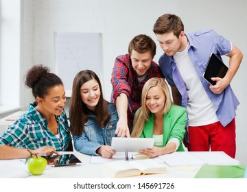 education concept - smiling students looking at tablet pc at school