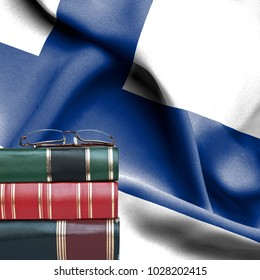 Education concept - Stack of books and reading glasses against National flag of Finland