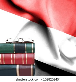 Education concept - Stack of books and reading glasses against National flag of Yemen