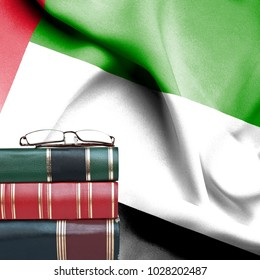 Education concept - Stack of books and reading glasses against National flag of United Arab Emirates