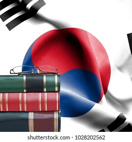Education concept - Stack of books and reading glasses against National flag of South Korea