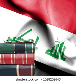 Education concept - Stack of books and reading glasses against National flag of Iraq