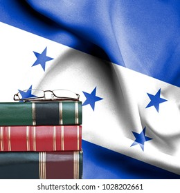 Education concept - Stack of books and reading glasses against National flag of Honduras