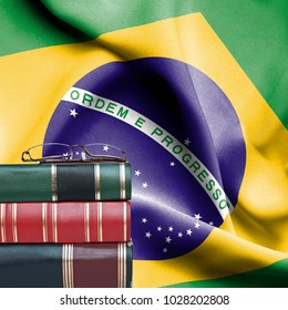 Education concept - Stack of books and reading glasses against National flag of Brazil