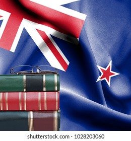 2e44aa3f21d8 Education concept - Stack of books and reading glasses against National flag  of New Zealand