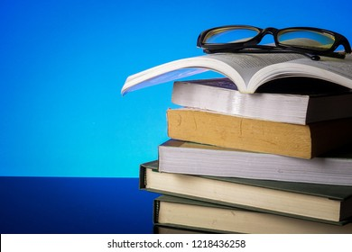 EDUCATION CONCEPT with stack of old book and reading glasses on a blue background.